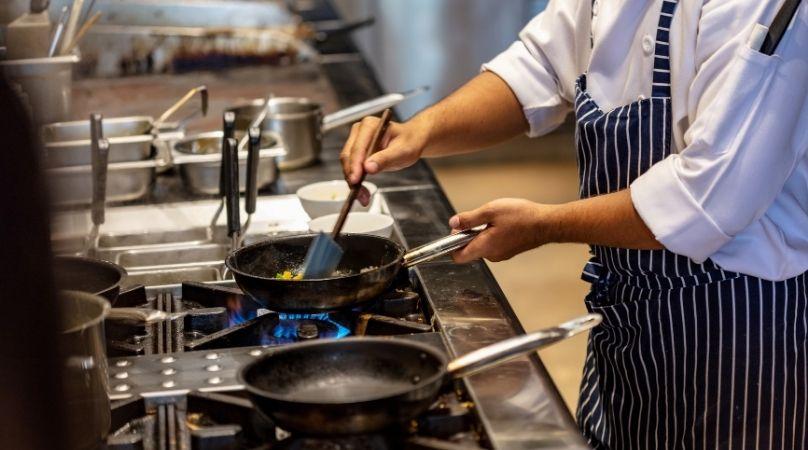 Chef cooking in dark kitchen